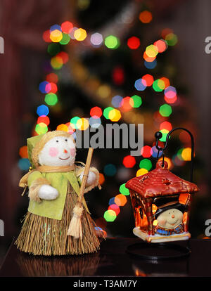 Christmas picture with a snowman and a flashlight on the background of a beautiful illumination in the form of bokeh from the festive lights on the Ch - Stock Photo