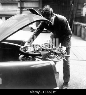 motorist putting folding bike in the trunk, 1965 - Stock Photo