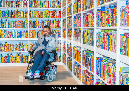 London, UK. 08th Apr, 2019. The British Library an installation by Yinka Shonibare CBE (pictured with his work), at Tate Modern, having just been acquired by them. Highlighting the impact of immigration on British culture, it is a site-specific installation with a digital platform for visitors to join in the discussion.It contains 6,328 books bound in 'Dutch wax print. The installation also contains an area for audiences to access information about the project on tablets. Credit: Guy Bell/Alamy Live News - Stock Photo