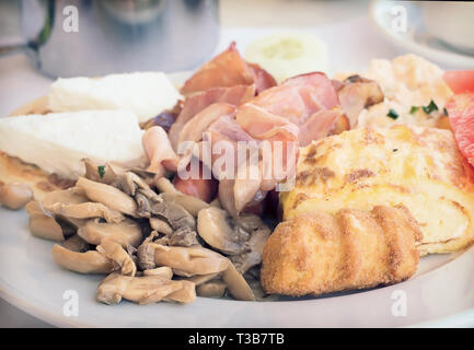Breakfast : scrambled eggs, ham , mushrooms and vegetables. - Stock Photo