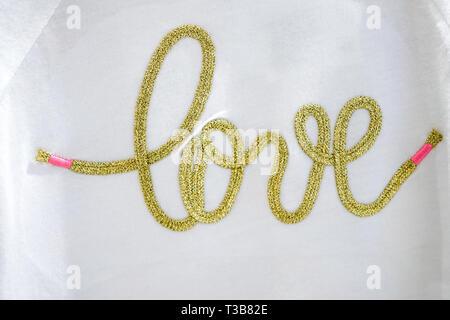 gold 'Love' typo knitting on the textile. - Stock Photo