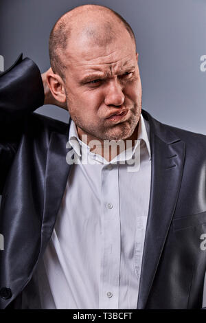 Unhappy stressed bald angry business man holding the head with very bad emotions in office suit on grey studio background. Closeup portrait - Stock Photo