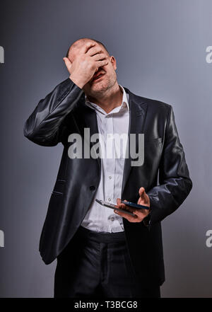 Unhappy stressed depressed business man holding in hand two mobile phones and covering the face the palm in office suit on grey background. Closeup po - Stock Photo