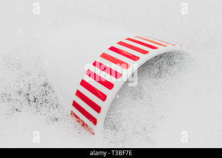close up of washing white cup with soap and water - Stock Photo