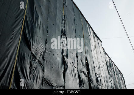scaffolding and safety net at residential building that is currently under renovation - Stock Photo
