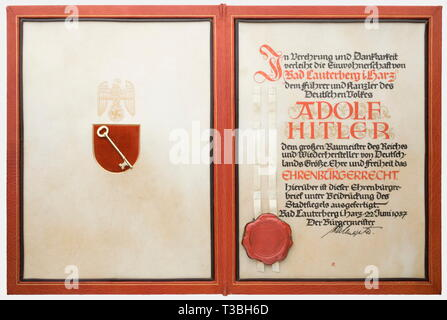 Adolf Hitler, a certificate of honorary citizenship awarded by the City of Lauterberg in the Harz Heavy, red leather folder bearing the city's coat of arms on the front. A sheet of parchment incorporated inside on the right with the corresponding calligraphic text granting rights of citizenship, dated 22 June 1937. It is signed by the mayor and has the city's great seal appended. On the left side a velvet shield bearing the key to the city with a gold painted national eagle above it. Dimensions ca. 44 x 33 cm. It comes with an old American exhibition label, '...taken from H, Editorial-Use-Only - Stock Photo
