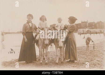 Vintage Photographic Postcard Showing Children Enjoying Donkey Rides on Margate Beach in Kent, England. Photo Taken in July 1915. - Stock Photo