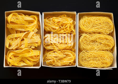 Set of various uncooked pasta in paper boxes on black background, top view. Close-up. - Stock Photo