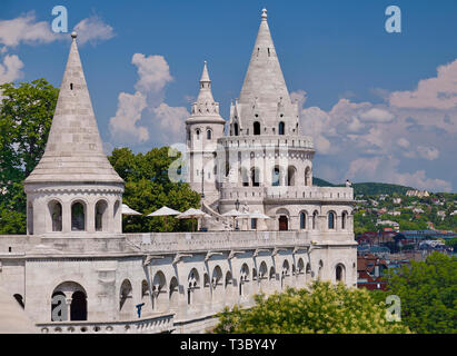 Hungary, Budapest, Castle Hill, Fishermans Bastion, Westernmost towers amidst trees and looking towards the western end of the city. - Stock Photo