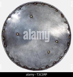 A German/Italian circular buckler, 2nd half of the 16th century Circular iron shield with turned-under and corded edge. Brass attachment rivets for the central handgrip with remnants of the leathering. The rim studded with brass coated decorative rivets, and small cracks at two places. Diameter 49 cm. Rare example of a circular buckler for use in the field. historic, historical, 16th century, defensive arms, weapons, arms, weapon, arm, fighting device, object, objects, stills, clipping, clippings, cut out, cut-out, cut-outs, utensil, piece of equ, Additional-Rights-Clearance-Info-Not-Available - Stock Photo