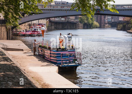 Man fixing sign on the Full Moo ice cream boat moored on the banks of the River Ouse in York with Lendal Bridge in background - Stock Photo