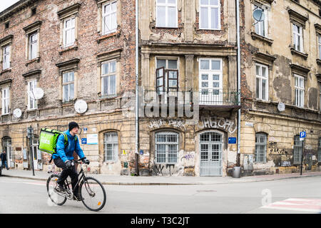 Krakow, Poland - March 22, 2019 - Uber eats delivery man in a cycle on an old town street - Stock Photo
