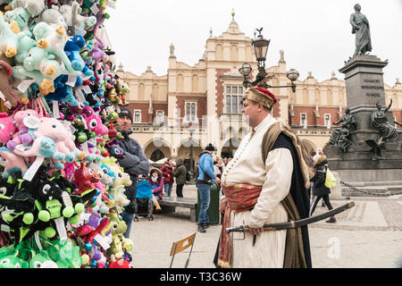 Krakow, Poland - March 22, 2019 - souvenirs, artist in traditional costume and Adam Mickiewicz Monument on Main Market Square - Stock Photo