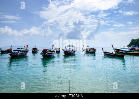 Wooden fishing long tail boat anchored on turquoise seashore with cloudy blue sky - Stock Photo