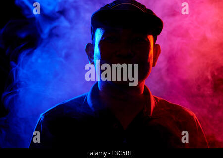 Portrait of Asian mature man in cap standing in the dark among smoke and looking at camera - Stock Photo
