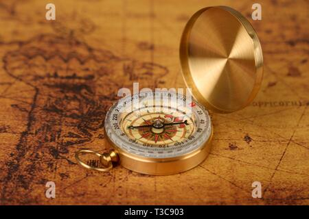 Vintage Compass lies on an ancient world map - adventure stories background - Stock Photo