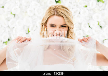 tricky young bride biting bridal veil on white floral background - Stock Photo