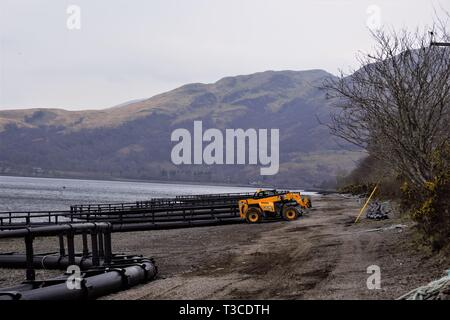Construction of Fusion Marine, HDPE, floating, salmon fish pen cages on the shores of Loch Creran. Hills in the background. - Stock Photo