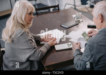 senior couple sitting at table with calculator, money and paperwork - Stock Photo
