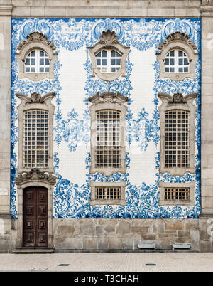 Blue and white painted ceramic tiles on a wall on the exterior of a church in Porto, Portugal. - Stock Photo