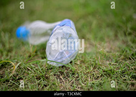 Discarded plastic water bottle on green grass field. - Stock Photo
