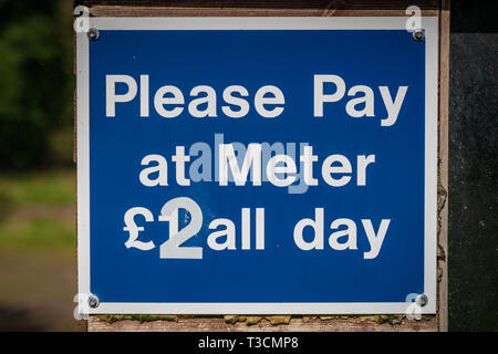 Sign: Please pay at meter, seen in Malmsmead in Devon, England, UK - Stock Photo