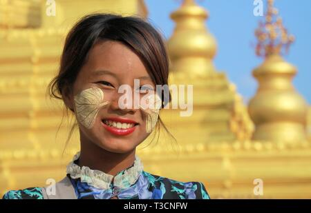 MANDALAY, MYANMAR - DECEMBER 17. 2015: Portrait of a Burmese girl with traditional Thanaka face painting in front of golden Pagoda at Kuthodaw Temple - Stock Photo
