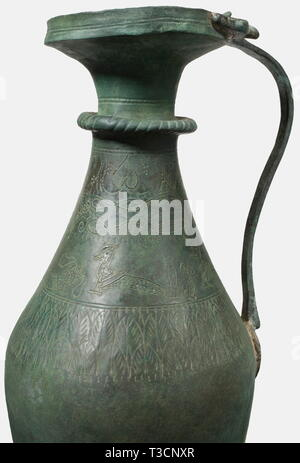 A Roman bronze ewer with silver inlays, 2nd - 4th century A.D. Bronze with greenish patina. Slender, slightly bellied ewer. Slender cordoned neck and widely flared rim. Narrow handle terminating in two animal heads. The shoulder surrounded by an engraved leaf frieze, surmounted by the punched and silver inlaid portrayal of two birds. Cleaned archaeological find. Restorations to the neck, rim, foot, and the right side. Height 30.5 cm. historic, historical, ancient world, ancient world, ancient times, object, objects, stills, clipping, cut out, cut, Additional-Rights-Clearance-Info-Not-Available - Stock Photo