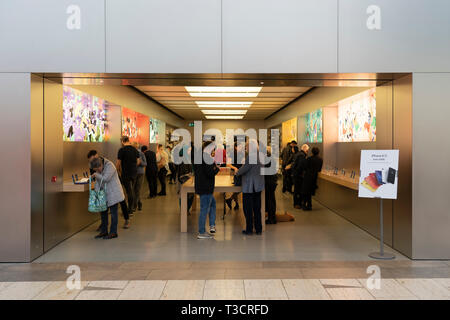 Customers browsing products in an Apple store in the Touchwood shopping centre, Solihull, UK - Stock Photo