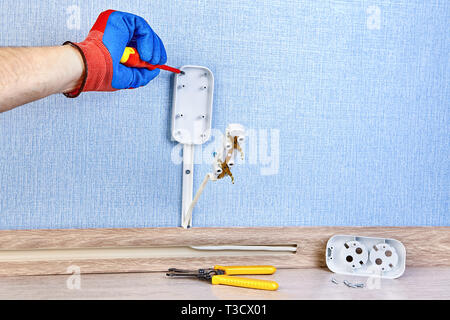 Electrician in protective gloves is twisting screw in new wall socket, residential wiring work. - Stock Photo