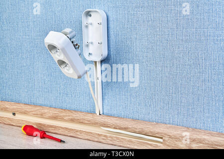 Duplex receptacle outlet in process of mounting, residential wiring work, close-up. - Stock Photo