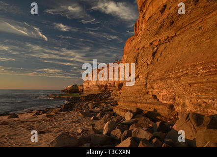 Waves from Pacific Ocean crashing on rocky shoreline along famous Sunset Cliffs, Point Loma, San Diego, CA, USA - Stock Photo