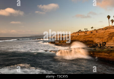 Waves from Pacific Ocean crashing on rocky shoreline along famous Sunset Cliffs Natural Park, Point Loma, San Diego, CA, USA - Stock Photo