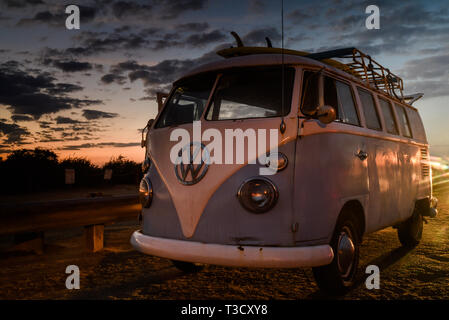 Vintage Volkswagon VW Microbus with rooftop rack for surfboards, parked along cliffs at Sunset Cliffs, San Diego, CA, USA - Stock Photo