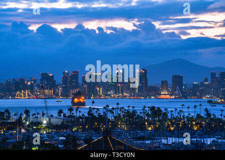 Calm sunrise, pre-dawn, over the San Diego skyline, with North San Diego Bay and docked sailboats off Shelter Island, California, USA - Stock Photo