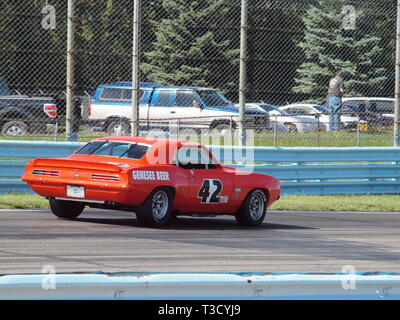 1969 Camaro Trans-Am race car at Watkins Glen race track during vintage race gathering in fall. Number 42 is seen entering first turn. - Stock Photo