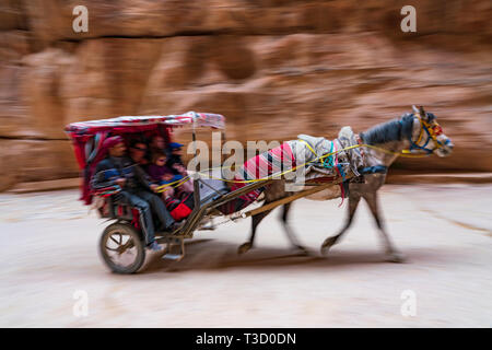 A horse carriage with tourists in the Siq the canyon leading to the main entrance to the ancient Nabatean city of Petra, Jordan. - Stock Photo