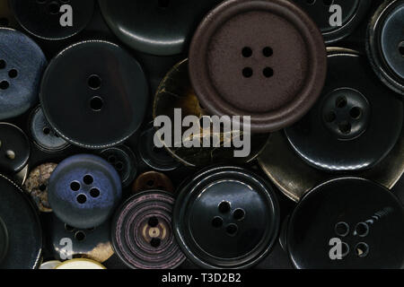 Various old and dark plastic and metal clothes buttons background - Stock Photo