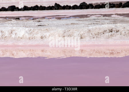 Reflections of salt evaportations in the pink colors of saline water during the production process in the salt fields of Fuencaliente, La Palma Island - Stock Photo