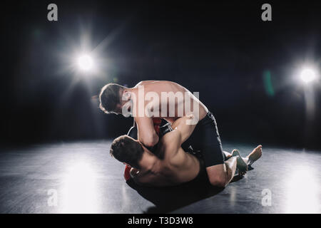 strong mma fighter in boxing gloves sitting on opponent and punching him in head - Stock Photo