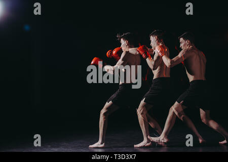 multiple exposure of strong shirtless muscular boxer doing punch - Stock Photo