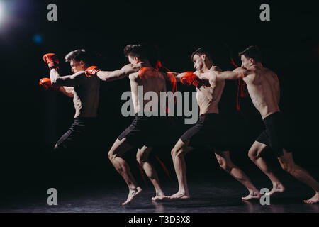 multiple exposure of strong shirtless muscular boxer in boxing gloves doing punch - Stock Photo