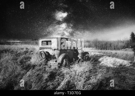A vintage four door car with one door open abandoned in tall grass under a star filled night sky in a black and white landscape - Stock Photo