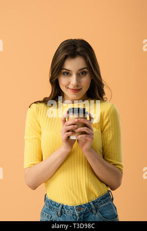 Front view of tricky brunette girl holding paper cup of coffee isolated on orange - Stock Photo