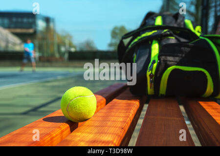 Tennis ball and sport bag on the bench on court. Concept of sport, healthy lifestyle. - Stock Photo