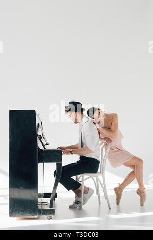 beautiful young ballerina leaning on pianist sitting at piano - Stock Photo