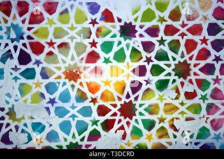 Old wall covered with an abstract colorful pattern, with flaking paint. - Stock Photo