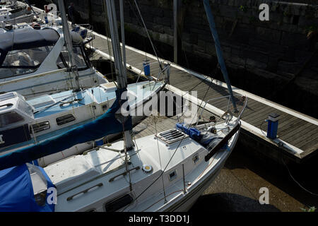 Boats moored to pontoon in Porthmadog marina at low tide in north wales uk - Stock Photo