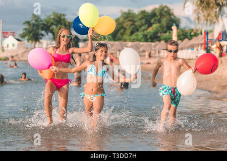 Happy children running together with balloons through the water at the beach - Image - Stock Photo