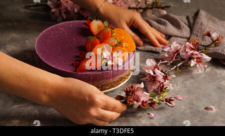 raw vegan cake with fruit and seeds, decorated with flowers - Stock Photo